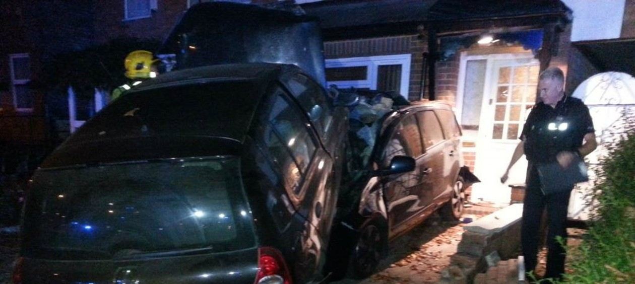 Utter destruction: The teenage driver of the black Reno Clio ploughed through a garden wall before landing on this vehicle.