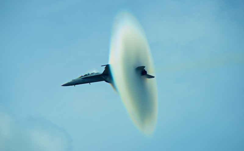 A vapour cone forms around the aircraft as it breaks the sound barrier