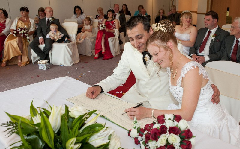 Kim and Carlos signing the wedding register at their joint wedding
