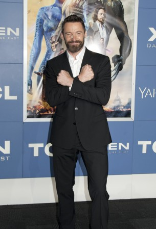 Hugh Jackman crosses his arms to make an X
