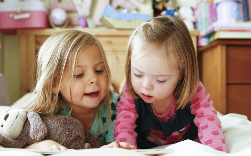 Evie reads a book with her younger sister Ellie.