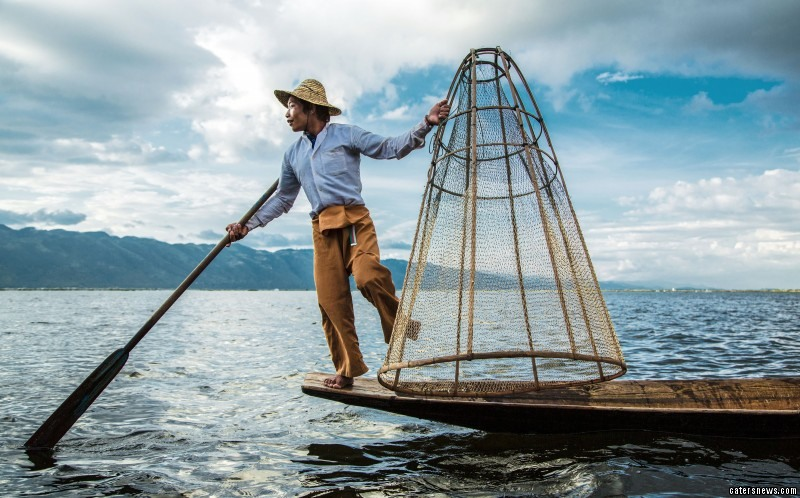 The upright leg-rowing technique allows fishermen to expertly navigate their boats through the dense Inle Lake