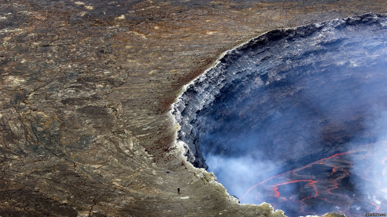 PIC FROM CATERS NEWS - (PICTURED: Francesco Pandolfo on the edge of Mount Nyiragongo) - Most people wouldnt even dream of going near an active volcano, well meet the man who goes INTO them, all in the name of science. Italian geologist Francesco Pandolfo had travelled to Africa to study the volcanic activity on Mount Nyiragongo in the Democratic Republic of Congo when he decided to get a closer look. He decided to abseil much closer to the smouldering lava than many would dare to go and was able to capture these stunning photographs of what a raging volcano really looks like. SEE CATERS COPY.