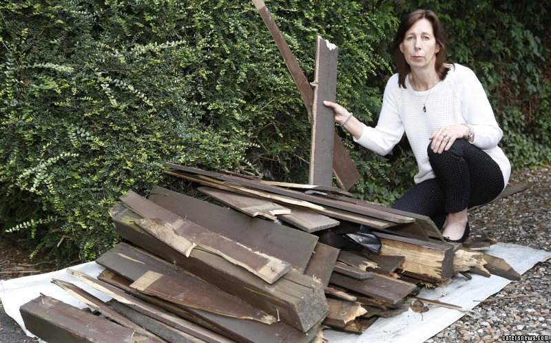 Alison Pinnock with broken wood piled from the fence destroyed by crashes