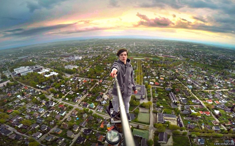 Ervin Punkar using a selfie stick to take a photo from the very top of the 600ft TV tower