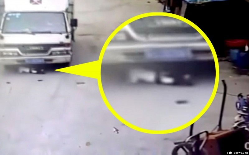 The boy quickly lies flat as the lorry reverses over him - saving his life