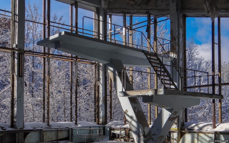 An abandoned swimming pool lies dusty and forgotten