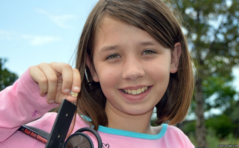 Alexis Davidson, 11 from Aurora Colorado, USA  holds up her tooth for the camera