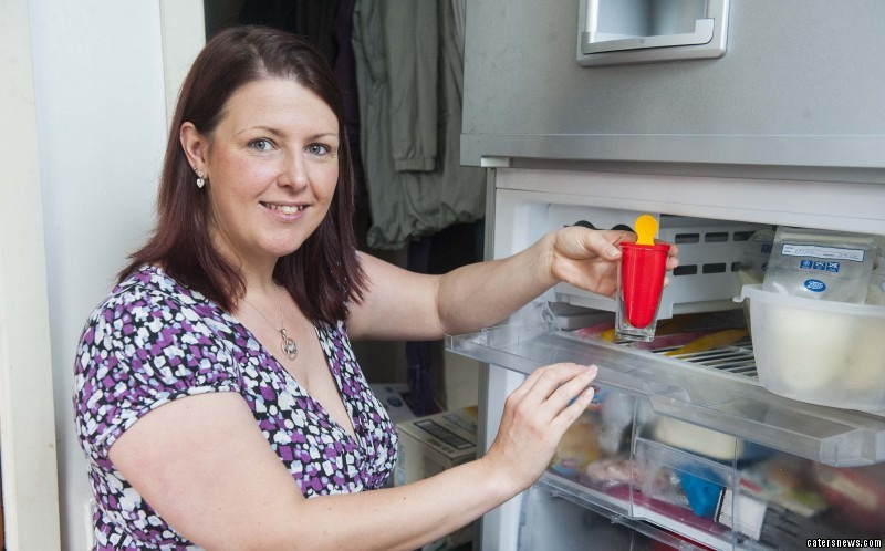 The mum puts the breastmilk lolly in the freezer to set
