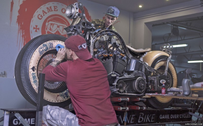PIC FROM GOS /CATERS NEWS - (PICTURED: designers at Cheyenne Bikes tattooing the bike)
