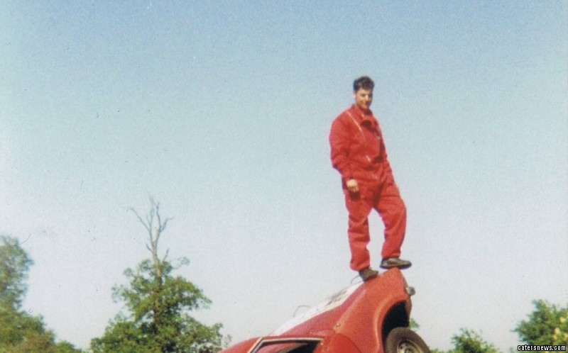 Mark stands atop of two rolled over cars