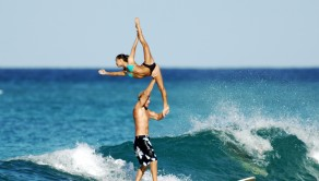 PIC BY MARK KLINTWORTH / CATERS NEWS - (Pictured: Chuck Inman and Lauren Oiye take part in some tandem surfing in Waikiki.) It takes a lot of skill to surf a wave just stood normally on a surfboard without falling over, but to hold different shapes in the air on the shoulders of a partner is even more challenging. That is what two daring people are doing in this incredible footage. The talented pair - Lauren Oiye and Chuck Inman - has been taking part in the Tandem Surfing competitions in Waikiki. Unlike the average surfing competition, Lauren and Chuck combine the balance needed to even stand up on a surfboard, with the strength needed to hold up various gymnastic poses. The dash-cams have captured the intricate manoeuvres Lauren has to make to get in to the shapes above Chuck in the air at break taking angles. The two friends have a remarkable bond, with the video showing their impeccable timing to synchronise with each other to get into these poses. SEE CATERS COPY.
