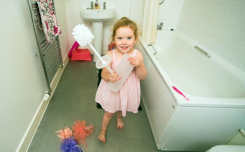 Lily Mullins holding a toilet brush in her bathroom - her condition Pica means she cannot stop trying to eat inanimate objects