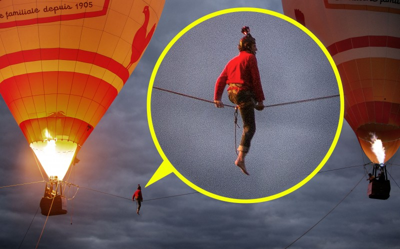 Juilen Millot rests on a tight rope between two hot air balloons