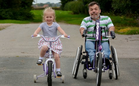 PIC BY SIMON KENCH/ CATERS NEWS - (PICTURED: Rich Willis learns to walk with daughter, Cherry, 4.) - Heres a father-daughter bond with a difference! Meet the adorable little girl whos formed a unique bond with her dwarf dad. Cherry Willis, 4, from North Frodingham, Yorkshire, helps her dad, Richard, 46, tie his shoe laces and even climbs up on him to get things out of the fridge. Richard suffers from diastrophic dwarfism  a condition stifling growth and leaving joints malformed which, in Richards case, has caused extreme arthritis and double scoliosis of the spine. Hes suffered a string of health problems, was forced to take a medical retirement in 2006 and needs a specialised wheelchair to support his movement. SEE CATERS COPY.