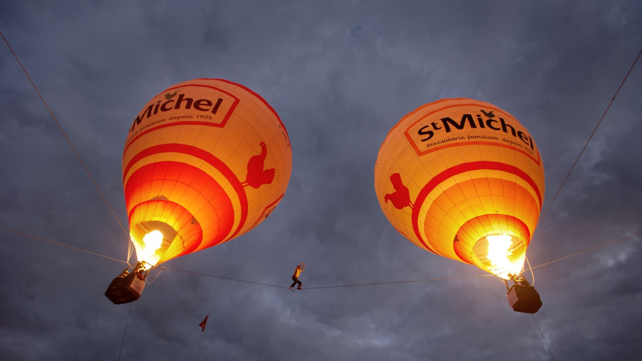 Tancrede Melet walks a tightrope between two hot air balloons