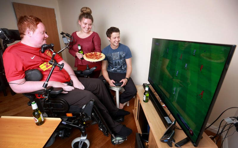 Will Clark playing on his Playstation with friends Megan Heap and Dan Home
