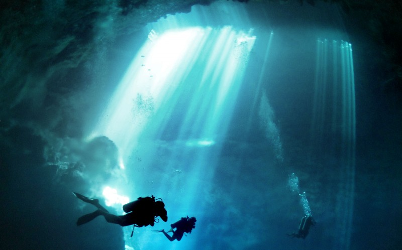 Light flitters down from above on three divers diving in a 400ft sinkhole deep in the Mexican jungle.
