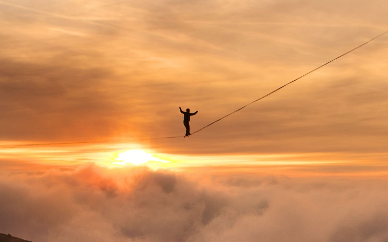 Samuel Volery walks a high-line over the mountains in Moleson, Switzerland. with the sunset washing over him