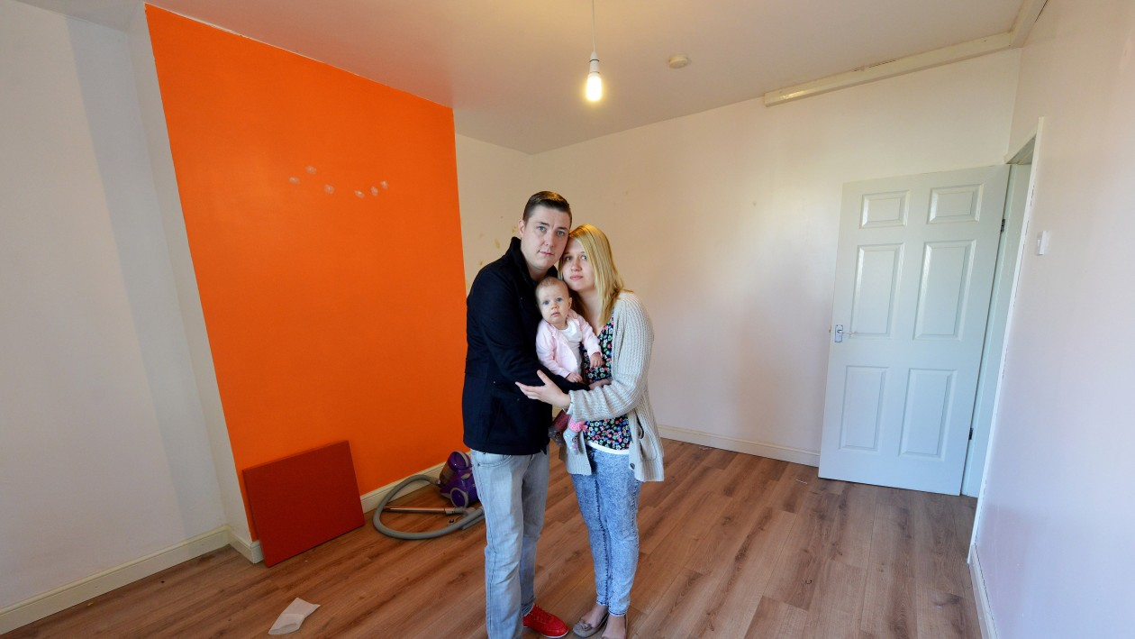 Becky Szenk with her partner Mark Higgins and their baby Ariyah in the living room