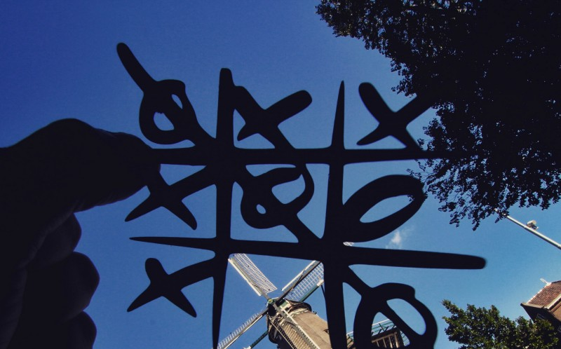 A PAPER CUT OUT OF NOUGHTS AND CROSSES IN FRONT OF DE GOOYER WINDMILL, HOLLAND