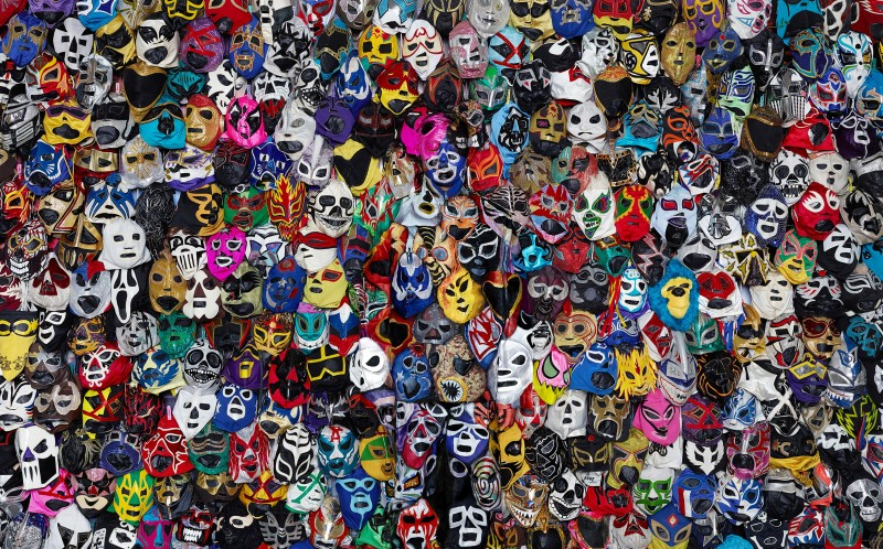 Liu disappears into the backdrop of Luchador wrestling masks