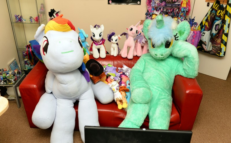 Ian Taylor at home watching the TV in his Brony suit with his collection beside
