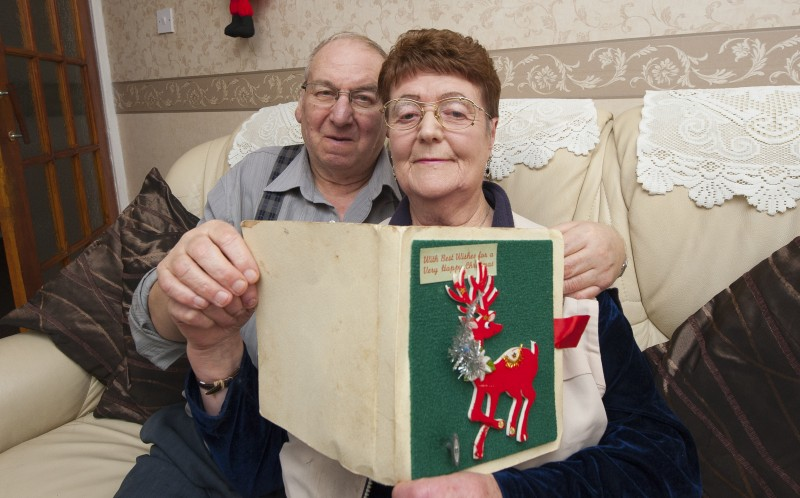 JOE AND BETTY RINKUS WITH THE CHRISTMAS CARD THAT JOE HAS GIVEN BETTY SINCE 1968