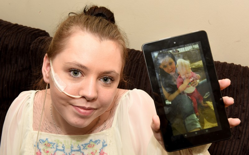 Saffron Taylor holding up a photo of her and her son Eden before the diagnosis