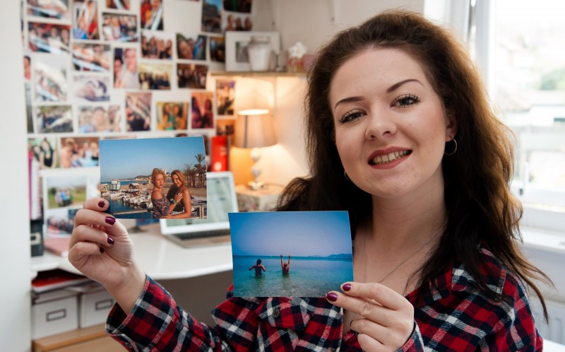 Laura Rose holding pictures of her and her friends on holiday she funded using money she made on Ebay
