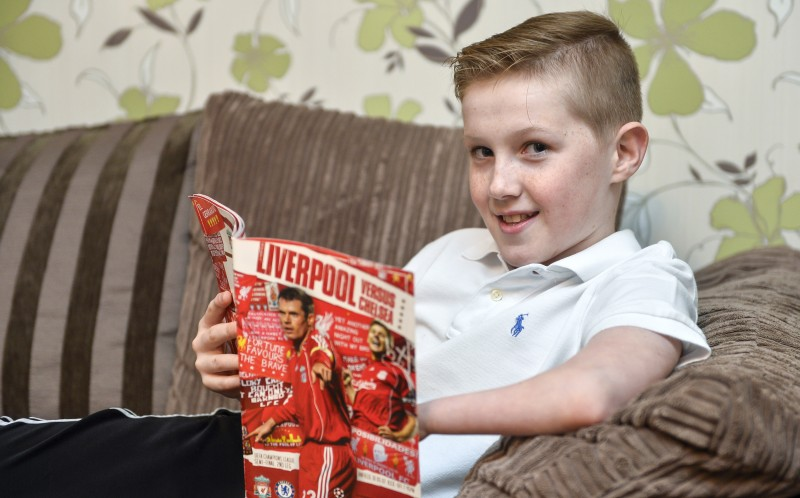 Thomas Atkinson reading his football magazine
