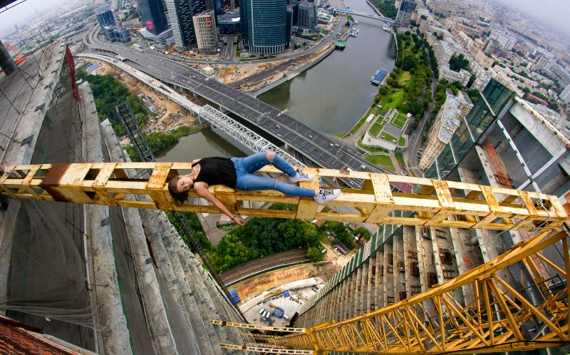 A Russian rooftopper relaxing on a crane over Moscow