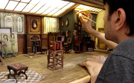 PIC FROM CATERS NEWS - (PICTURED: Ali Alammeedee, 33 working on the house) - Its a small world! These incredible scenes like good enough to be real, that is until you take a step back. The settings are in fact intricately detailed dioramas, which are so good that there are even tiny portraits hanging from the walls. The meticulous painting projects usually require miniaturist Ali Alammeedee, 33, from Kerbala, Iraq, to spend two to three months patiently painting every inch of the settings and are made using hundreds of metres of wood, plastic and copper. For the project, which shows a photography studio from the 1900s, Ali carefully researches every item that will eventually comprise part of the diorama in order to make sure it is historically accurate. SEE CATERS COPY.