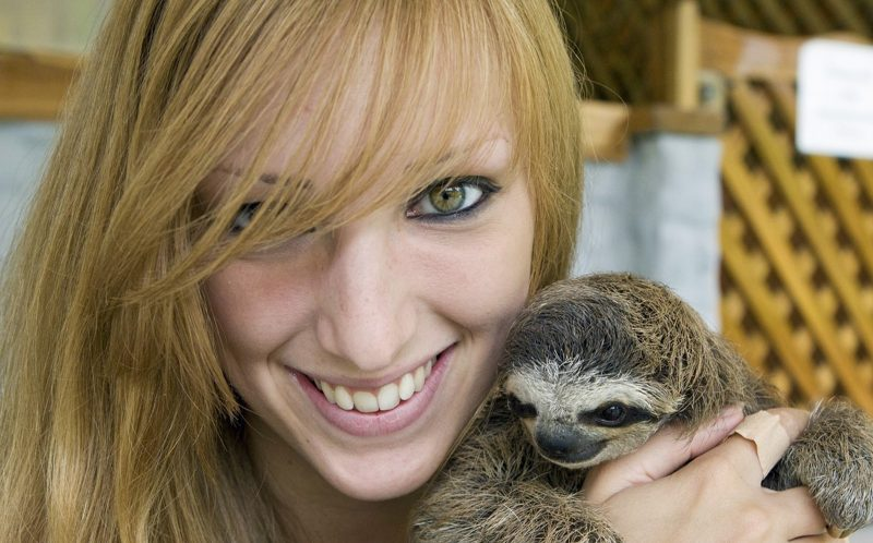 Zoologist Becky Cliffe poses with a sloth