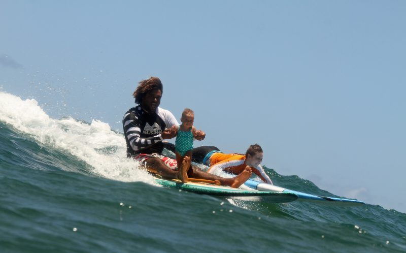 SERGIO LIMA / CATERS NEWS - Now the daughter performs impressive stunt by balancing on his hand while he surfs.
