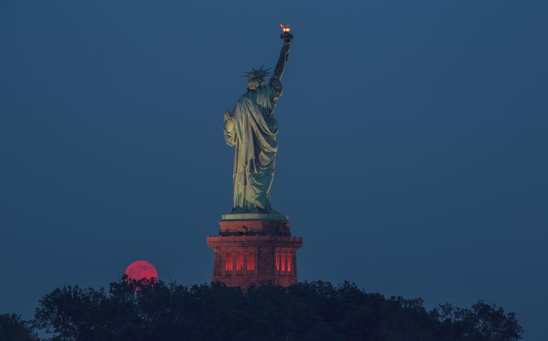 JIMMY KASTNER / CATERS NEWS - Statue of Liberty caught in rare moment where full moon coincided with the summer solstice..