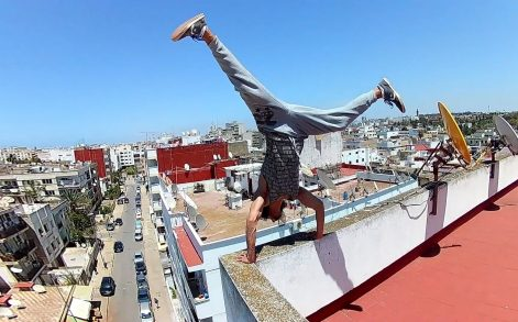 KHALID TENNI / CATERS NEWS - Khalid Tenni performs a handstand on a rooftop.