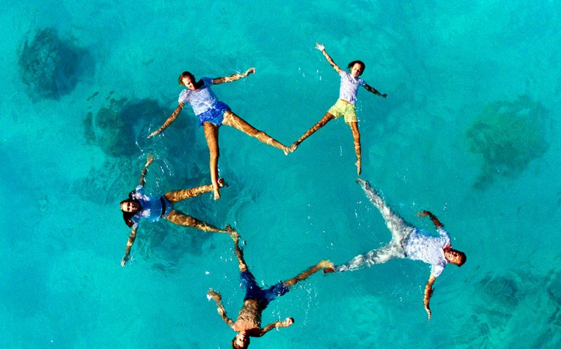 PIC BY HELENE HAVARD - (PICTURED: A wedding party poses on for a drone on their wedding day.) - These stunning images capture loved-up newlyweds snuggling up in deserted exotic locations. Crystal clear waters, lush palm trees and quaint beach huts form the stunning backdrops to the devoted duos. Wedding photographer Helene Havard from Papeete, French Polynesia, incorporates the couples into such vast scenes to illustrate how they appear to be in their own romantic world together. SEE CATERS COPY.