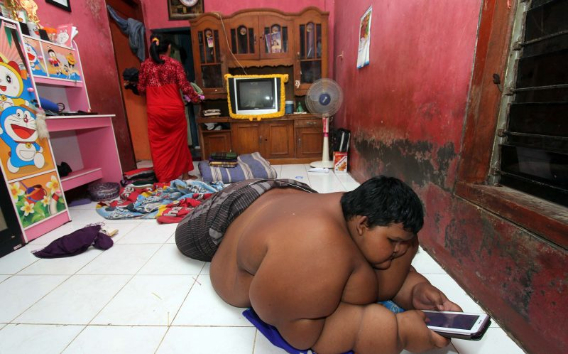 PIC FROM SIJORI IMAGES/CATERS NEWS - (PICTURED: Arya Permana 10-years-old is a giant boy from West Java Province, Indonesia.) - A ten-year-old is being put on a crash diet for fear he may die - after scoffing his way to becoming the worlds fattest child. Arya Permana weighs an eye-watering 192kg and is categorised as morbidly obese. His rapid weight-gain has forced him to quit school because he can no longer physically walk. Arya scoffs five meals a day consisting of rice, fish, beef, vegetable soup and Tempeh - a traditional soy patty - which alone is normally enough to feed two adults. And because of his astonsihing weight, his parent shave been unable to find clothes that fit him, leading to him wearing just a sarong. SEE CATERS COPY.