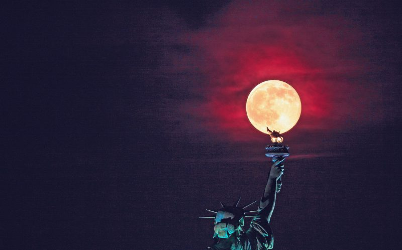 PICS BY JIMMY KASTNER / CATERS NEWS - (PICTURED: Statue of Liberty caught in rare moment where full moon coincided with the summer solstace last Monday leaving torch looking like its alight - photographs by Jimmy Kastner) - Stunning shots capture the rare moment the Statue of Liberty looked like it was ablaze as a glorious glowing sunset appeared above the torch. James Kastner, 31, from Somerville in New Jersey, USA, caught the vivid moment the full moon rose above the tip of torch during the summer solstice. The rare occurrence, which happened on June 20, is not predicted to be seen again until 2062. The clear sky, taken on the longest day of the year, amplified the crimson glow of the moon as it climbed over Liberty Island. The statue was designed by French sculptor Frdric Auguste Bartholdi and gifted to America in 1886 as a symbol of lasting friendship by the two nations. It depicts the Roman goddess Libertas, the embodiment of liberty, holding a tablet inscribed with the date of Americas Declaration of Independence on July 4, 1776, and the torch to welcome immigrants arriving into the country. - SEE CATERS COPY