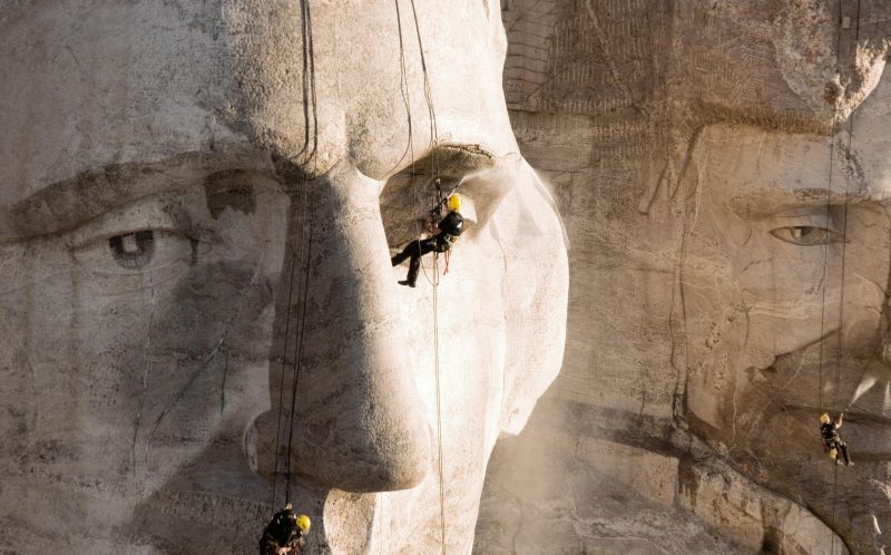 PIC FROM CATERS NEWS -  Two men cleaning Mount Rushmore in South Dakota.