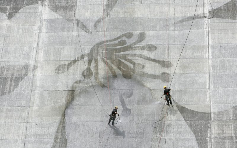 PIC FROM CATERS NEWS - Two men clean the Matsudagawa Dam in Japan.