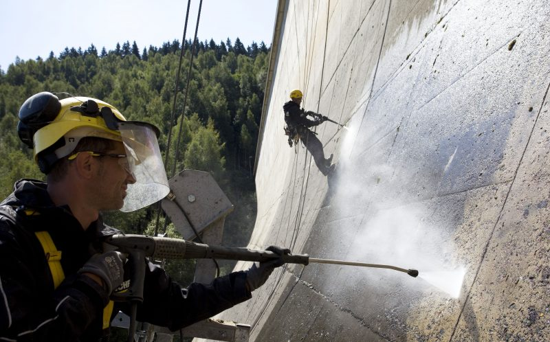 PIC FROM CATERS NEWS -  Two men clean the Eibenstock Dam in Germany.