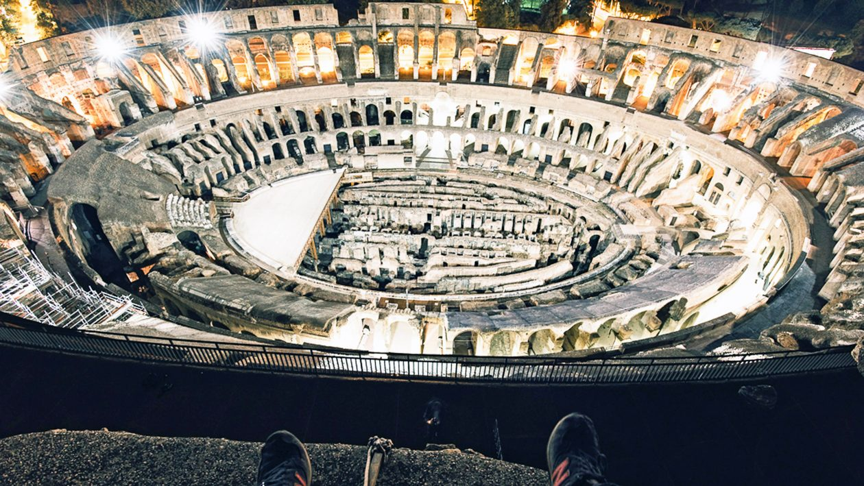 PIC BY Flavius Vasily/ CATERS NEWS - (PICTURED: A man climbs up to the top of the Colossuem in Rome, Italy.) - The world-famous colosseum in Rome is once again the site of daredevil bravery. Flavius Vasily, from Kassel,Germany, scrambled over the fence under the cover of darkness to sneak past security. Once inside, he took his own tour of the ancient gladiatorial arena and photographed its majestic beauty at night. Flavius, 23, and a friend only had one shot to make the stunt work - they had a one day layover in Rome before flying on to South Africa and Thailand. SEE CATERS COPY.