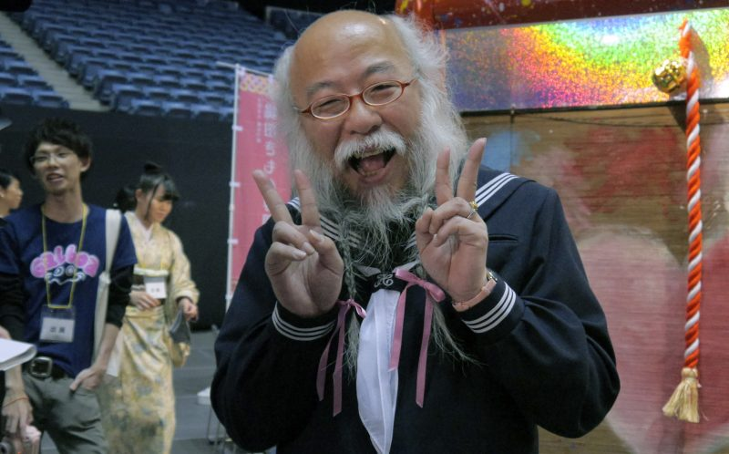 PIC FROM CATERS NEWS - (PICTURED: Hideaki Kobayashi dressed as a school girl) - This is the overjoyed face of a Japanese man who dresses as a schoolgirl at the weekend. Hideaki Kobayashi, 54, began the bizarre campaign after a friend told him anyone over 30 who wore a schoolgirl outfit got free ramen. But despite not having much luck on the free noodle front, Hideaki has continued to dress himself in the traditional Sailor Uniform Ojisan, complete with ribbons in his beard. He has since travelled to China, Osaka and France after building quite a following, with many referring to him as that old man wearing a girls sailor uniform. SEE CATERS COPY.