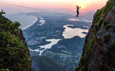 PIC BY RAFAEL MOURA/MEDIA DRUM WORLD/CATERS NEWS - PICTURED: RIO DE JANEIRO, BRAZIL: BRAVE slackliners have been pictured walking the ropes above Rio de Janeiro, with the half a mile drop showing the city in all its glory. The stunning shots show the daredevils tread across an eighty-two-foot-long high line on Pedra da Gvea mountain with an amazing sunrise illuminating the city landscape behind. The images were captured by Brazilian photographer Rafael Moura (30) and show how lucky fans and athletes are to be in Rio for this Olympics. The lead up to Rio 2016 has been riddled with problems as fears persist over the Zika virus while ten people were recently arrested on suspicion of planning terrorist attacks during the Olympics.Despite this, Rafael felt the city was ready to welcome the world with open arms. SEE CATERS COPY. **FOR USE AND SALE IN USA ONLY**