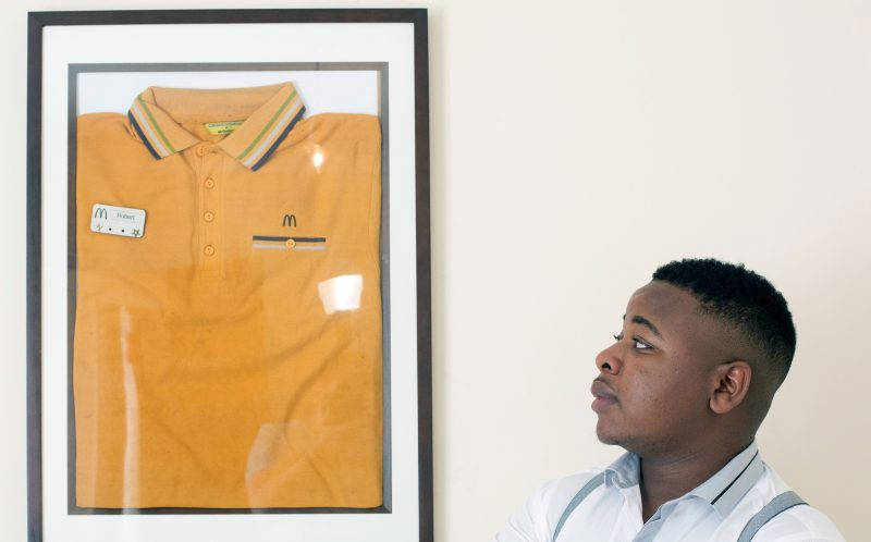 PIC FROM CATERS NEWS - (PICTURED: Robert looks at his uniform, which is now framed in a portrait.) - A teenage trader swapped shifts at the golden arches for a one-of-a-kind gold supercar after working his way up from water boy to millionaire trader. When Robert Mfune of Southampton turned 16 years of age he worked at McDonalds and ran errands for binary traders all while still at college. By the time Robert passed his A Levels with grades AAB, he was a Bentley owning millionaire who had only just stopped serving Big Macs. SEE CATERS COPY.