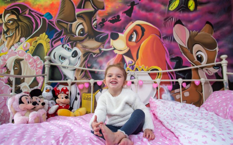 PIC BY HARRY WHITEHEAD/ CATERS NEWS - (PICTURED: Bobbie Hargreaves, aged 3, pictured in her bedroom, in front of the amazing Disney Mural, painted by Bobbies dad Adam.) - A supermarket worker gave his daughter the bedroom of every little girls dreams when he decided to help her sleep at night by hand painting her own Disneyland. Genie-us Yorkshire dad Adam Hargreaves has become an internet sensation after winning the bedtime battle with his three-year-old daughter with a spectacular wall mural. Overwhelmed by the reaction to his viral video, Adam, 27, hopes to pack in the day job of stacking shelves to take his hobby full time. SEE CATERS COPY.