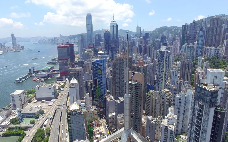 **MANDATORY BYLINE PIC BY ANDREJ CIESIELSKI AND JAMES SIGHT / CATERS NEWS - (PICTURED: Andrej Ciesielski takes a picture from the roof of 118 Connaught Road West in Hong Kong's Sheung Wan district.) - A drone pilot pulled off a stunt not even remotely safe - after flying a drop atop a skyscraper. Singapore-based German explorer Andrej Ciesielski managed to scale 118 Connaught Road West in Hong Kong's Sheung Wan district. Once there, the 19-year-old took stunning clear photos and drone footage of the city and bay stretched out 162 metres below. However, he and his friend James Sight were caught on the way back down before being released by police. SEE CATERS COPY