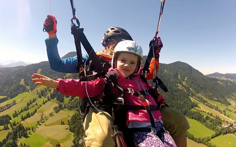 PIC BY MIK BROSCHART/ CATERS NEWS - (PICTURED: Emilia smiles at the camera while she paraglides with her father Mik in Germany. ) - This little girl loves to do a little PARA-GLOATING as she soars above the clouds with her dad. Little daredevil Emilia often shouts hey, were higher than you to other paragliders as she flies as high as possible with her father Mik. She also doubles as a handy camerawoman, filming their flights under bright blue skies. The pair often paraglide at the Brauneck mountain, the nearest place to their family home in Lenggries, Germany. SEE CATERS COPY.